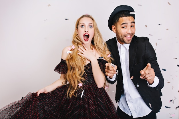 Portrait astonished excited woman with long blonde hair in luxury dress with funny handsome guy having fun in tinsels. celebrating great party, smiling