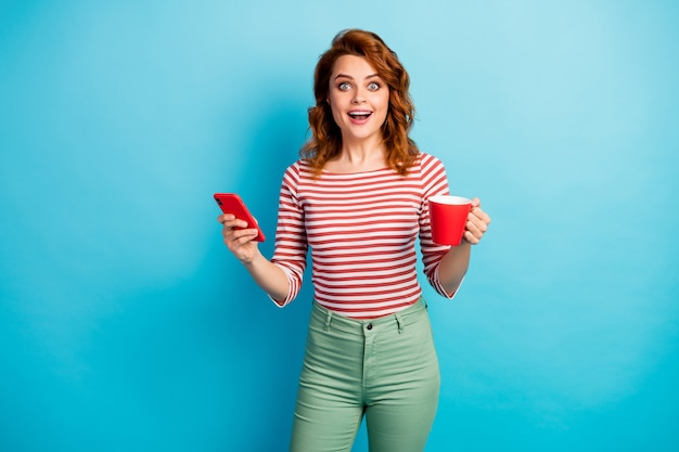 Portrait of astonished girl use mobile phone search find sales website impressed scream wow omg hold cup with cacao wear green pants white trousers isolated over blue color