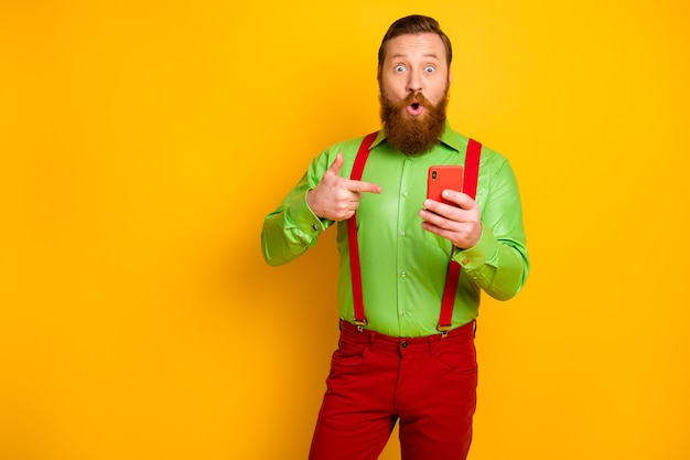 Portrait of astonished man use smartphone search social media discount news impressed point index finger multimedia recommend wear pants isolated over shine yellow color