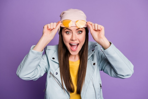 Portrait of astonished positive cheerful girl youngster cant believe her eyesight touch spectacles impressed scream wear look good outfit isolated over purple color background