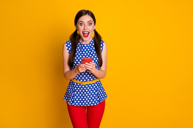 Portrait of astonished positive girl use smartphone impressed social media feedback wear trendy pants isolated over bright shine color background
