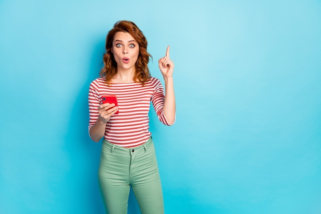 Portrait of astonished woman use cellphone chatting post think thoughts have question answer raise index finger up impressed scream wow omg wear sweater isolated blue color