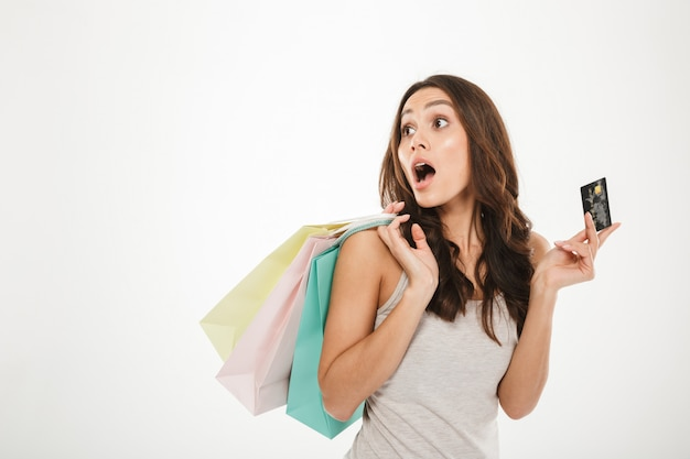 Portrait of astonished woman with lots purchases in hand doing shopping using credit card, isolated over white