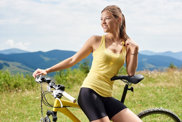 Portrait of athlete girl female cyclist sitting on yellow mountain bicycle, enjoying summer day in the mountains. outdoor sport activity, lifestyle concept