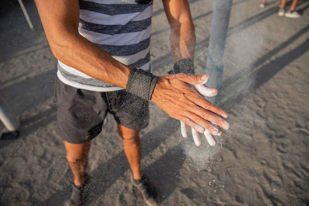 Portrait of an athlete's hands applying weightlifting chalk powder for training with weights - sportsman using equipment during training concept.