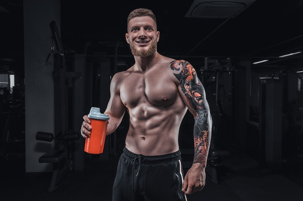 Portrait of an athlete standing with a shaker in the gym. bodybuilding and fitness concept. mixed media