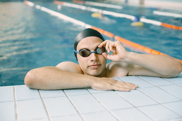 Portrait of athlete swimmer in a cap at side in swimming pool. swimmer in indoor pool getting out of water.