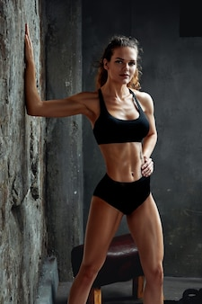 Portrait of athletic caucasian attractive fit woman dressed in top and leggins, against stone wall background. sport, fitness, crossfit.
