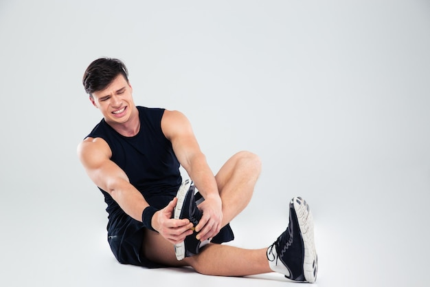 Portrait of athletic man suffering from pain in ankle isolated
