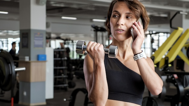 Portrait of athletic mature woman is making set of reps exercise for biceps with dumbbells in hands in gym. she is speaking mobile phone. life and sport concept.