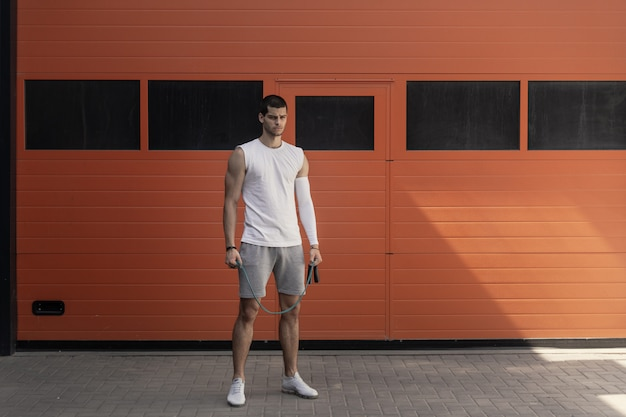 Portrait athletic, muscular man preparing for warming up with jumping rope