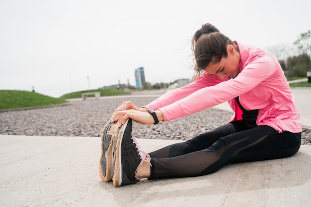 Portrait of an athletic woman stretching legs before exercise outdoors. sport and healthy lifestyle.