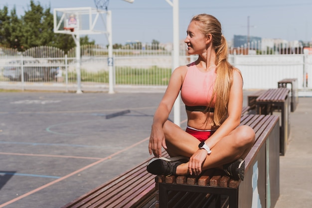 Portrait of an athletic, young girl in sportswear and glasses sitting on the playground