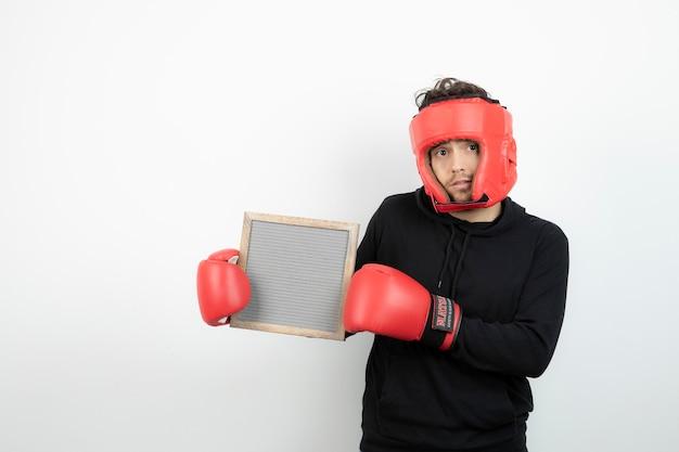 Ritratto di giovane atletico in cappello rosso di boxe che tiene cornice vuota.