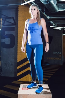 Portrait of an athletic young woman standing on wooden box in fitness box