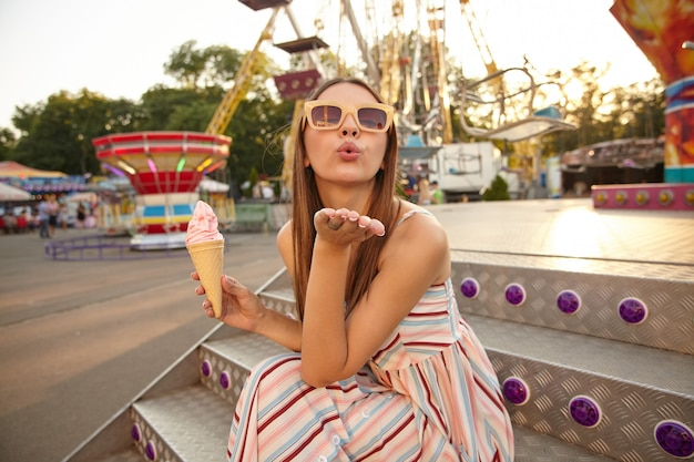 Ritratto di attraente giovane donna bruna con i capelli lunghi in posa all'aperto in una calda giornata di sole, seduto sulle scale e tenendo il gelato in cono, alzando il palmo e soffiando aria bacio
