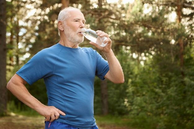 Portrait of attractive active male pensioner with bald head and stubble refreshing himself after jogging outdoors, standing against pine forest, holding bottle of drinking water