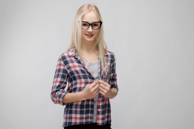 Portrait of attractive adorable blonde teenager girl in checkered clothes in glasses on gray