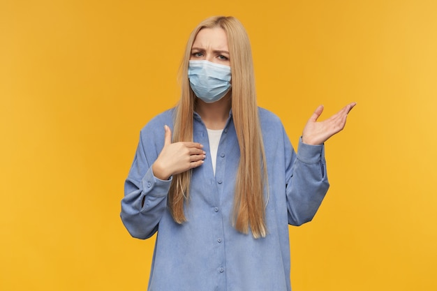 Portrait of attractive, adult girl with blond long hair, confused and raised her hand. wearing blue shirt and medical face mask. watching at the camera, isolated over orange background
