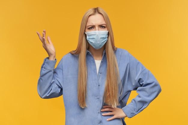Portrait of attractive, adult girl with blond long hair. wearing blue shirt and medical face mask. confused and angry. raised her hands. watching at the camera, isolated over orange background