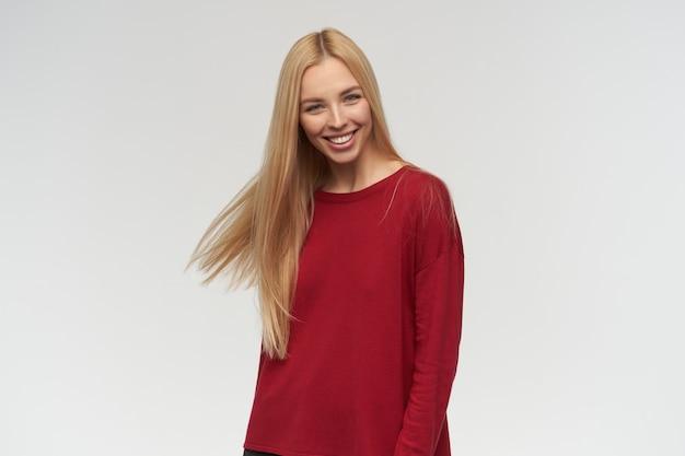 Ritratto di attraente, ragazza adulta con capelli lunghi biondi. indossare un maglione rosso. concetto di persone ed emozione. guardando la telecamera, isolata su sfondo bianco