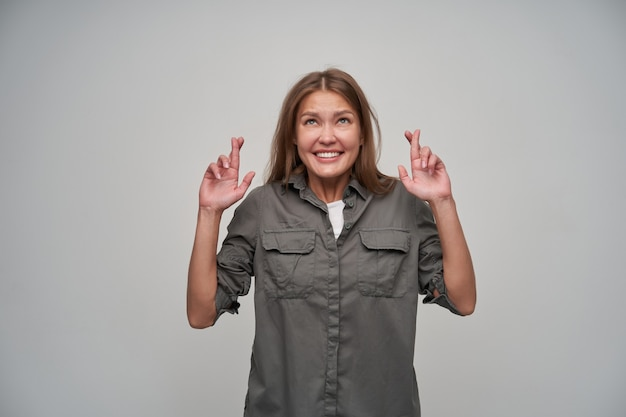 Portrait of attractive, adult girl with brown long hair. wearing grey shirt and keep her fingers crossed. within temptation. watching up at copy space, isolated over grey background
