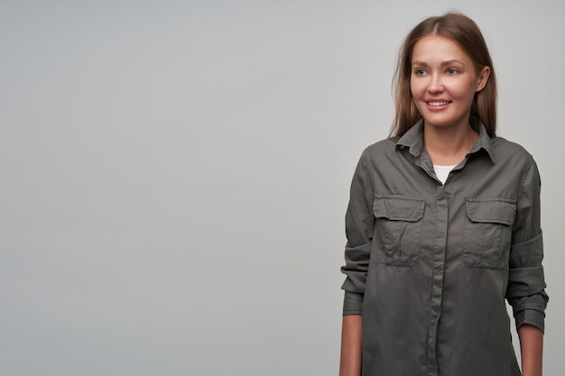 Portrait of attractive, adult girl with brown long hair. wearing grey shirt and smiling. confident posture. watching to the left at copy space, isolated over grey background