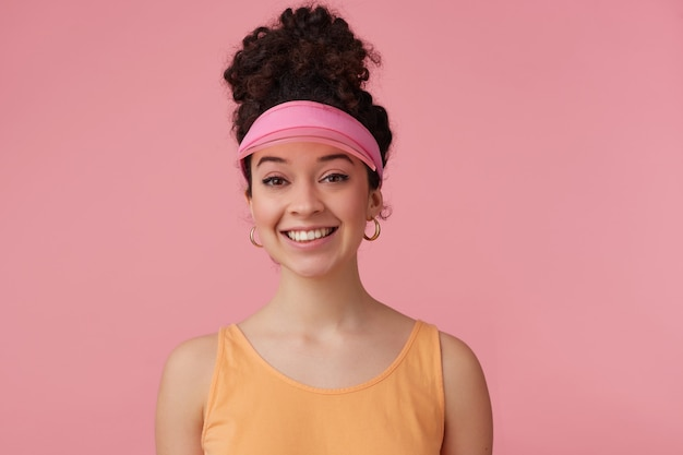 Portrait of attractive, adult girl with dark curly hair bun. wearing pink visor, earrings and orange tank top. has make up