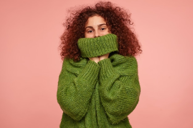 Portrait of attractive, adult girl with ginger curly hair. wearing green turtleneck sweater and pull a sweater over her face. isolated over pastel pink wall