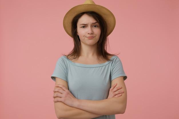 Ritratto di ragazza attraente e adulta con lunghi capelli castani. indossa una maglietta e un cappello bluastri. piega le mani su un petto. incredulo isolato su muro rosa pastello