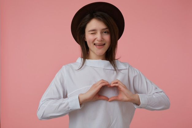 Portrait of attractive, adult girl with long brunette hair. wearing white blouse and black hat. showing love sign. emotion concept. watching and wink  isolated over pastel pink wall