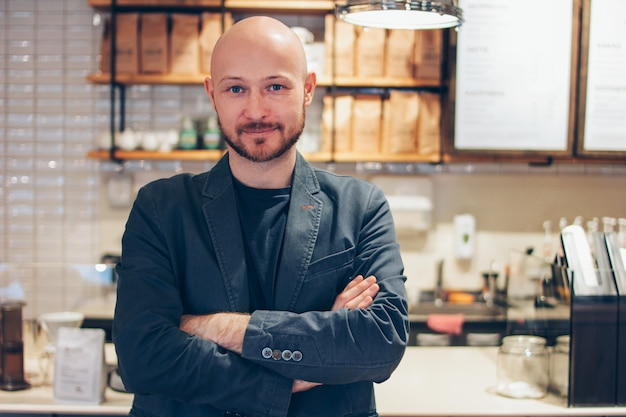 Portrait of attractive adult successful bald bearded man in suit on cafe coffee house background