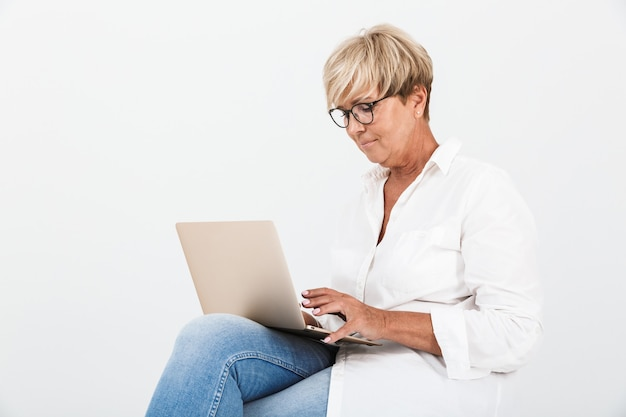 Portrait of attractive adult woman wearing eyeglasses sitting with laptop computer isolated over white wall in studio