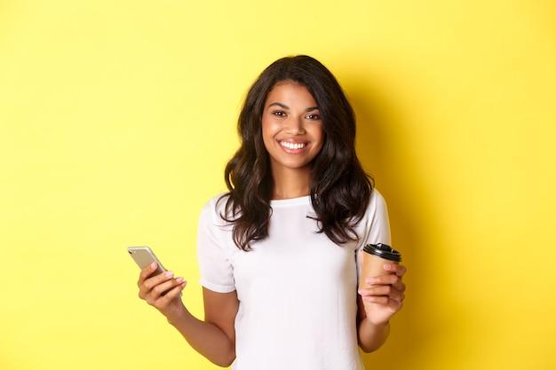 Ritratto di una ragazza afroamericana attraente che sorride, che tiene in mano una tazza di caffè e un telefono cellulare, in piedi su uno sfondo giallo.