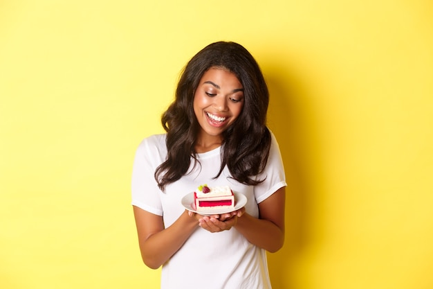 Portrait of attractive african-american woman, looking at delicious piece of cake and smiling, standing over yellow background