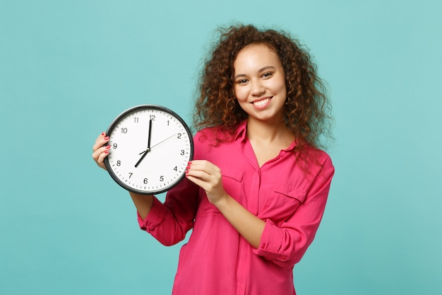 Portrait of attractive african girl in pink casual clothes holding round clock isolated on blue turquoise wall background in studio. people sincere emotions, lifestyle concept. mock up copy space.