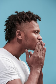 Portrait of attractive afro-american man with air kiss isolated over blue