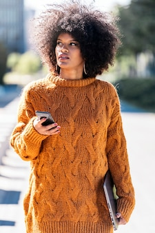 Portrait of attractive afro woman using mobile phone in the street. business woman concept