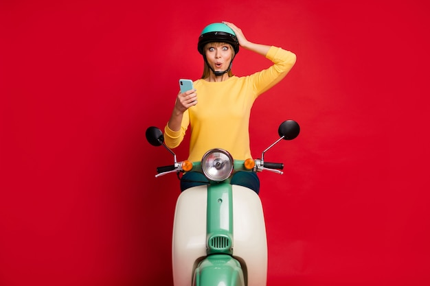 Portrait of attractive amazed cheerful girl sitting on moped using cell reading news
