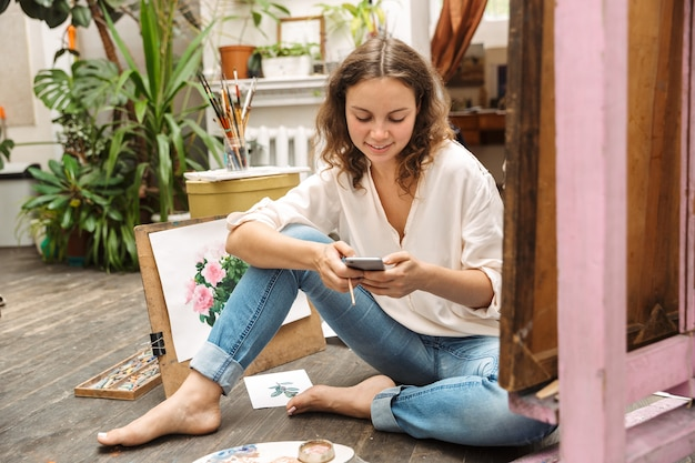 Portrait of attractive artistic woman sitting on floor and holding cellphone while drawing picture on paper with paint palette in workshop or master class