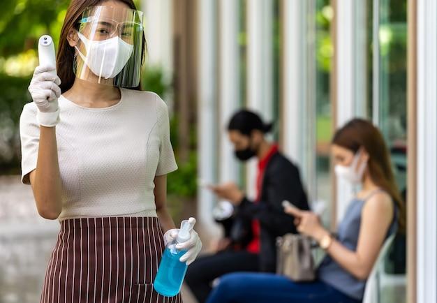 肖像画の魅力的なアジアのウェイトレスは、キューで待っている社会的な距離の顧客の背景を持つフェイスマスクとシールドホールド温度計とアルコールゲル消毒剤を着用しています。新しい通常のレストランのコンセプト。