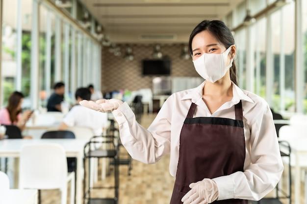 肖像画の魅力的なアジアのウェイトレスはフェイスマスクを着用します。新しい通常のレストランのライフスタイルコンセプト。