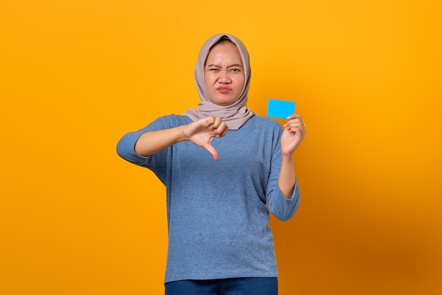 Portrait of attractive asian woman holding credit card and showing dislike sign with thumbs down
