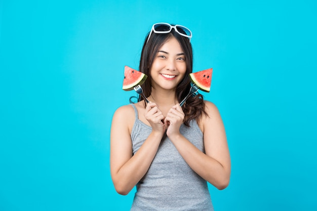 Portrait attractive asian young woman holding two piece slide of watermelon and wearing fashion sunglasses on isolated blue wall, copy space and studio, diet and healthy fruit concept