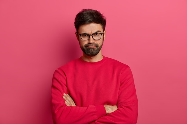 Il ritratto di un giovane barbuto attraente tiene le mani incrociate, esprime un'opinione negativa su qualcosa, sorride per insoddisfazione, qualcuno infastidito dice bugie, indossa guanti e maglione rosso.