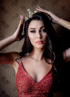 Portrait of an attractive beautiful brunette girl dressed in red dress with make-up in the precious crown