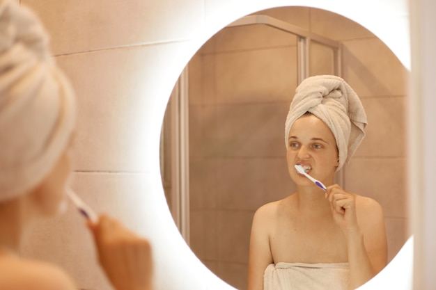 Portrait of attractive beautiful woman with towel on her head standing in front of the mirror in the bathroom and brushing her teeth, hygiene procedures in the morning.
