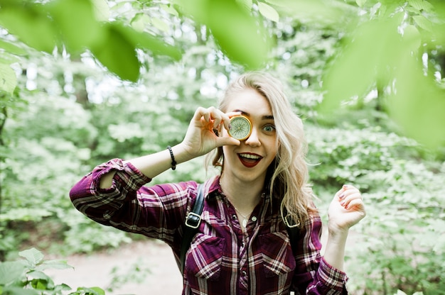 Portrait of an attractive blond girl posing with a compass in a forest.