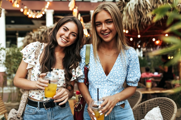 Portrait of attractive blonde and brunette girls in stylish floral blouses and denim pants smiling widely and holding lemonade glasses outside