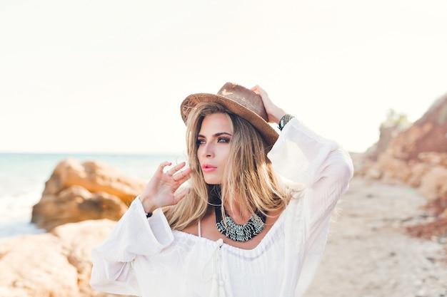 Ritratto di attraente ragazza bionda con i capelli lunghi in posa per la fotocamera sulla spiaggia rocciosa. indossa camicia bianca, cappello, ornamenti.